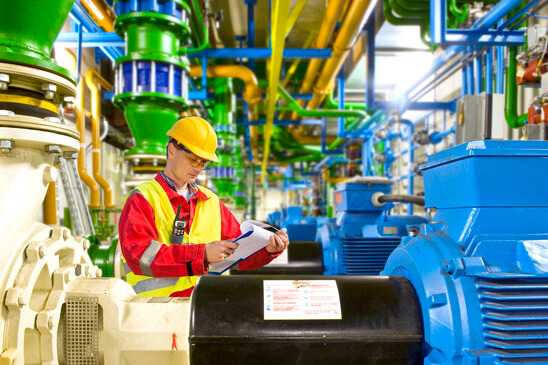 Engineer looking at a 5S supplies checklist during maintenance work in a large industrial engine room
